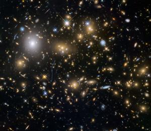 Las observaciones del telescopio Hubble, recurriendo a la técnica de lente gravitacional, han revelado uno de los grupos más grandes de las primeras galaxias (y más tenues) del universo. Algunas de ellas se formaron sólo 600 millones de años después del Big Bang. Crédito: ESA/NASA