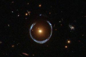 Esta imagen muestra el efecto de la lente gravitacional. La galaxia roja (en el centro) distorsiona la luz de una galaxia azul muchísimo más distante. Crédito: ESA/Hubble & NASA