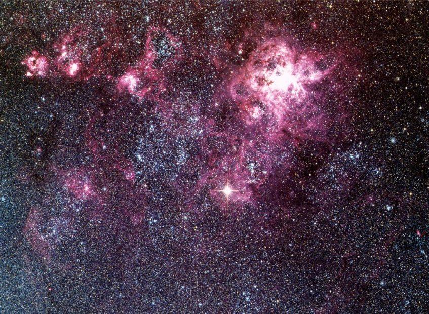 A supernova 1987A (estrela brilhante no centro) junto à região gigante de formação estelar NGC2070, também conhecida por 30 Doradus ou Nebulosa da Tarantula. Crédito: ESO.