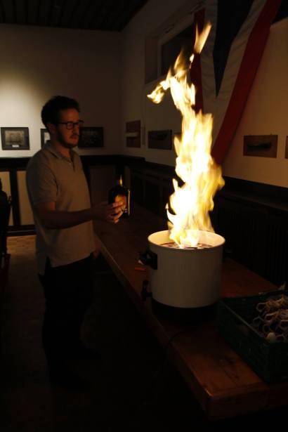 Der Vorsitzende entzündet die Feuerzangenbowle.