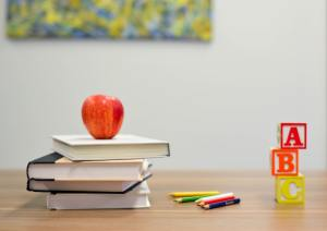 [A pile of books, an apple, and block letters on a school desk]