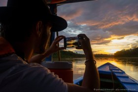 Photographing the sunset with iPhone from the boat on Tambopata River, Peru