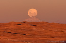 The full moon is rising just above the 190 km distant Llullaillaco volcano on the Argentine border