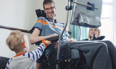 Man in wheelchair with Tobii Eyegaze computer attached smiles at child. woman looks on