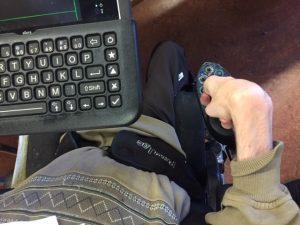 Person holding onto power wheelchair joystick