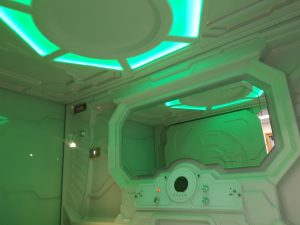 inside the sensory pod with green mood lighting. Control console and mirror at centre on frame