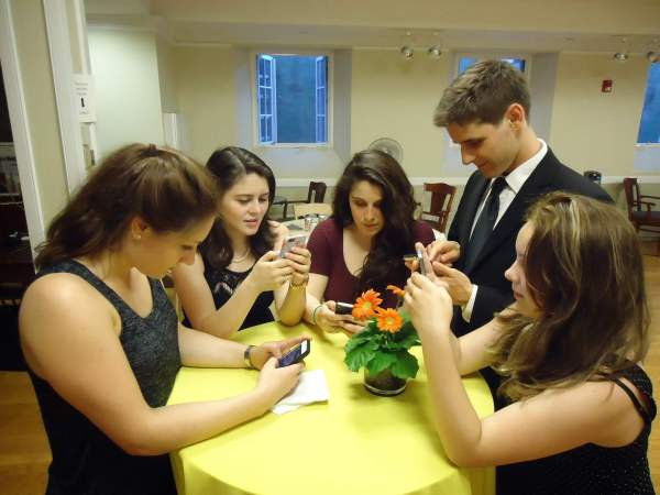 Five teens around a table at a social event all staring at there mobile phones.