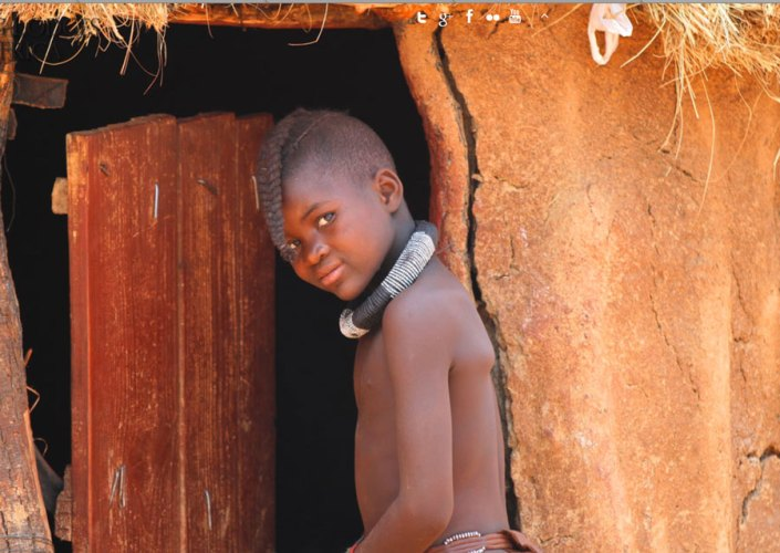 Young Himba boy entering his home