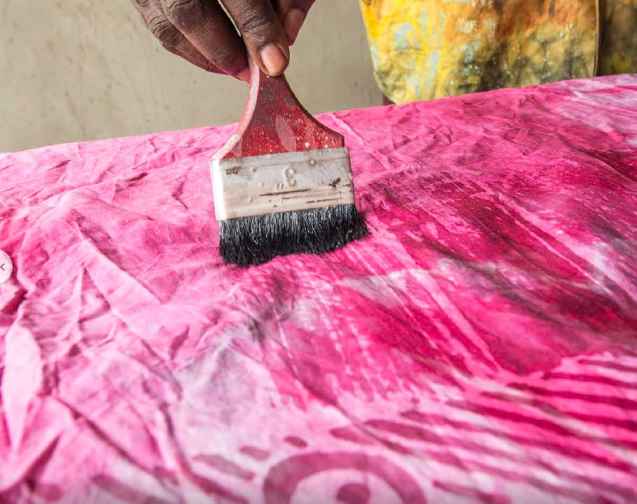 Handmade Batik In Ghana brushing the cloth with wax