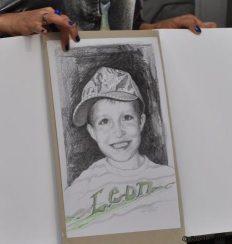 Isabella Blauauge überreicht das Überraschungsgeschenk, ein Portrait, dass den Schulanfänger Leon genau zeigt wie er ist.