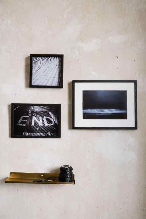 Wand mit drei Bildern in schwarzen Rahmen, Messingregal mit schwarzem Packband