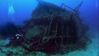 ship wreck on the side and diver swimming by