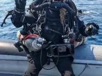 female rebreather diver on rib ready to dive