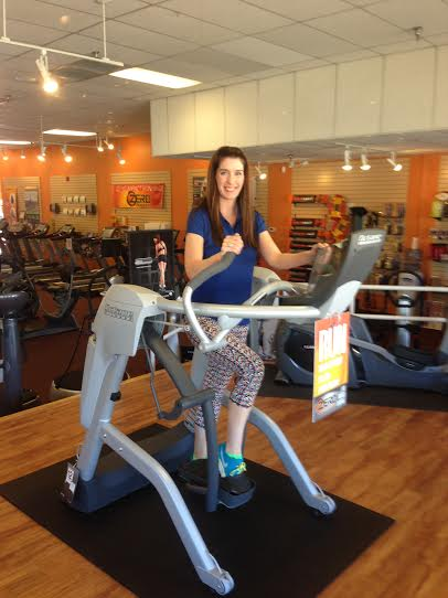 "At Home Fitness store manager Jaime Janman stands on the brand new Octane Zero Runner. The Michigan native said she enjoys working for AHF because the company ""really cares about its employees and customers."""