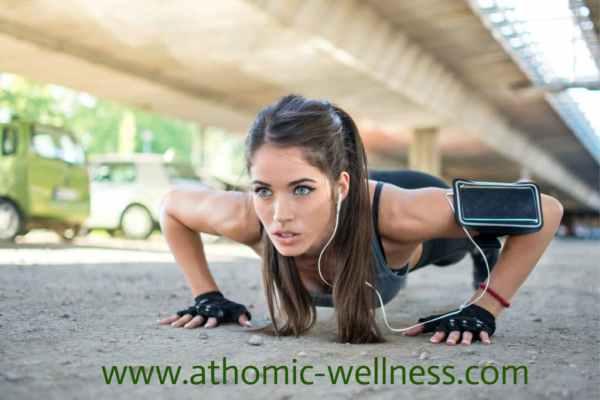 Jeune sportive aux yeux clairs faisant du personal training. Elle s'entraine physiquement en faisant la planche abdominale. Elle a des écouteurs dans les oreilles.