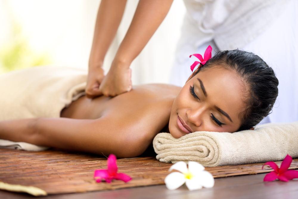 Photo d'un thérapeute massant le dos d'une jolie et jeune femme. Elle a les cheveux noirs avec une fleur rose. Elle ferme les yeux et sourit.
