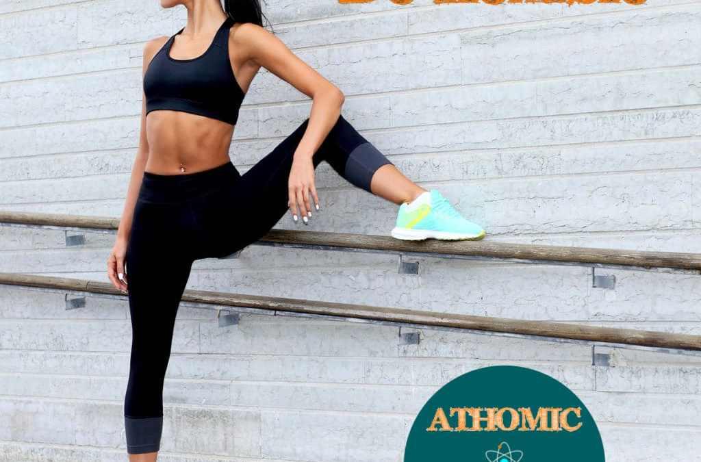 Solutions pour traiter la lombalgie. Jeune femme se tient dos au mur et montre sa souplesse et sa flexibilité de hancheSouplesse et flexibilité pour lutter contre le mal de dos - Athomic Wellness
