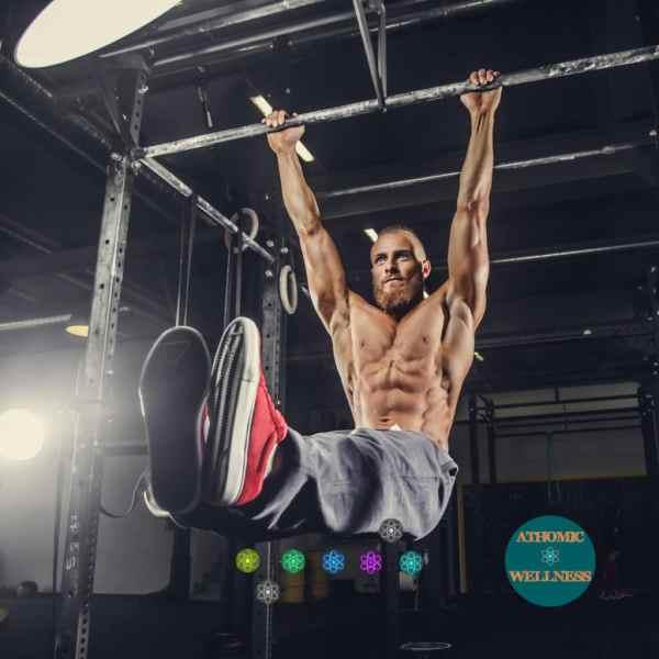 Homme suspendu à une barre fixe. Il est torse nu avec ses muscles abdominaux apparents. Ses jambes sont à l'équerre pour une préparation physique. Suspension à la barre de traction