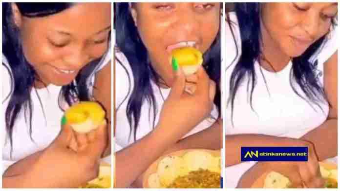 lady swallows morsels of Banku