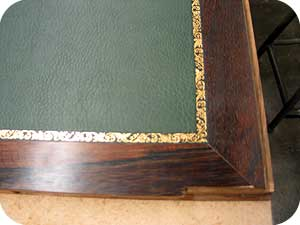 recouvrement en tissu enduit avec une vignette louis xvi sur un dessus de porte de secretaire