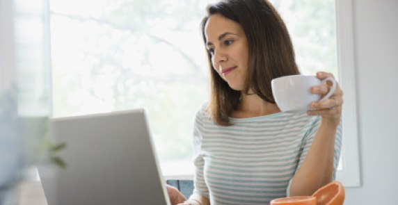 woman sitting at computer holding cup of coffee