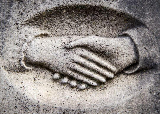 Clasped hands on stone grave stone