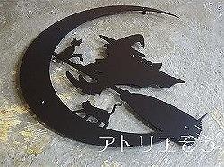 アトリエそうオーダーメイドデザイン制作のロートアイアン風アルミ製妻飾り。魔女と猫が月をバックに箒で飛んでいるかわいいステンレス製妻飾りの写真
