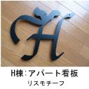 イニシャルHとリスのモチーフを組み合わせたロートアイアン風ステンレス製マンションH棟の看板の写真
