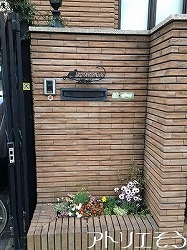 アトリエそうオーダーメイドデザイン制作のロートアイアン風錆に強いステンレス製の表札です。犬と小麦を組み合わせたとても素敵な表札の設置写真です。