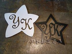 ロートアイアン風錆に強いステンレス製星の中にイニシャルYとKをデザインした素敵な妻飾りの写真