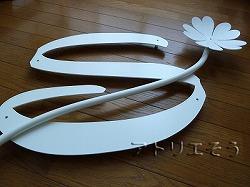 イニシャルSに五つ葉のクローバーを加えた白塗装のステンレス製妻飾り。