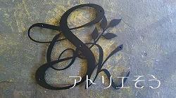 イニシャルSとTとKに葉を組み合わせたアルミ製妻飾り