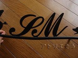 イニシャルSM+フライングピックの表札です。ロートアイアン風アルミ製表札です。