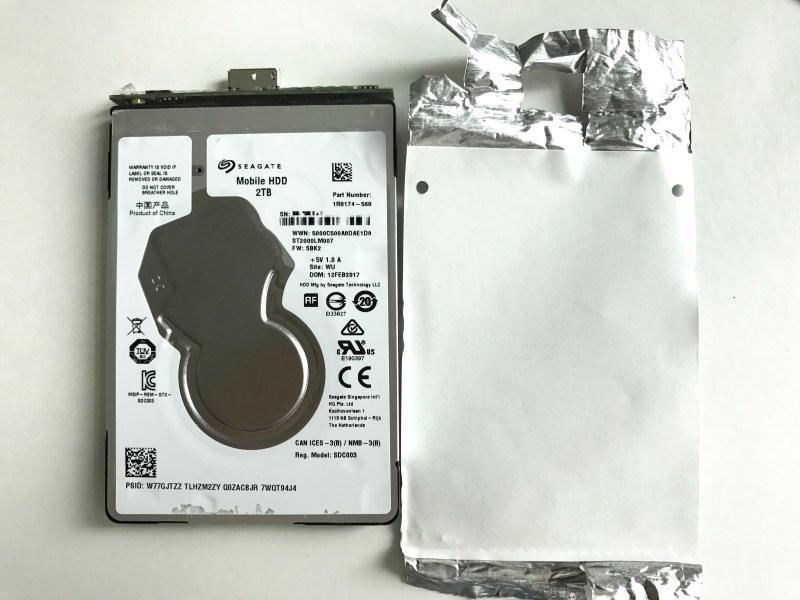 Peeling off the metallic sheet protecting the hard drive