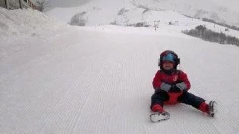 criança descendo neve de trenó