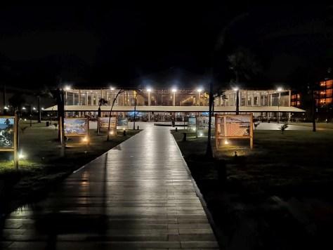 #PraCegoVer Audiodescrição: fotografia noturna de um prédio iluminado com alguns painéis na frente e uma passarela em primeiro plano