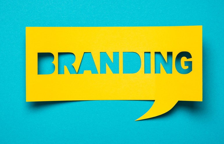Yellow paper with the word branding cut out shows image and branding