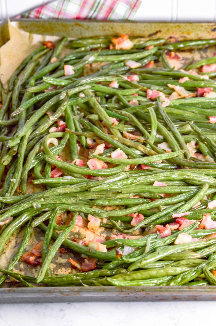 Bacon Green Beans on a metal baking sheet with parchmaent paper. The background at the top is white with a red/white and green plaid towel. www.atwistedplate.com/bacon-green-beans/