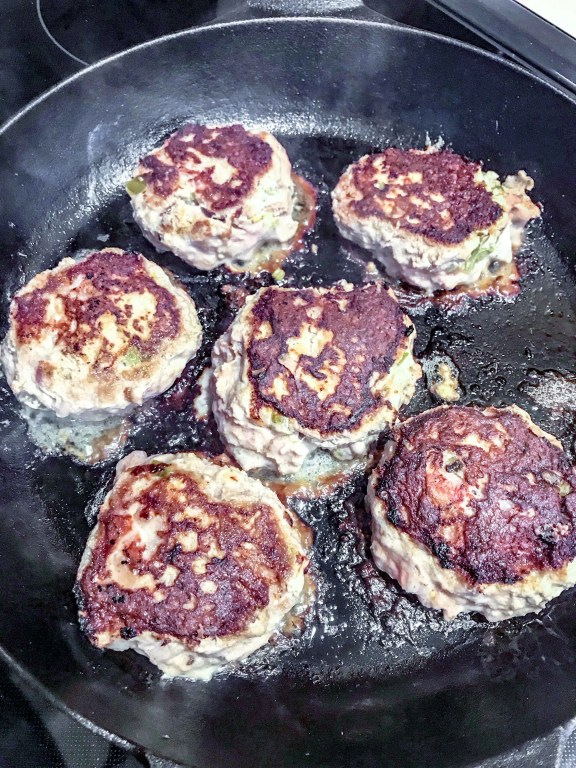 Image of 6 Bacon Jalapeño Turkey Burgers cooking in a cast iron skillet. www.atwistedplate.com/jalapeno-bacon-turkey-burgers/