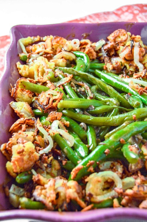 Close up angle view of Dairy Free Green Bean Casserole in a purple dish on a pink towel.  https://www.atwistedplate.com/green-bean-casserole-gluten-dairy-free/