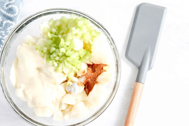 Bowl of cooked cubed Potatoes, celery, mayonnaise and spices. In the background with a spatula. https://www.atwistedplate.com/old-bay-potato-salad/