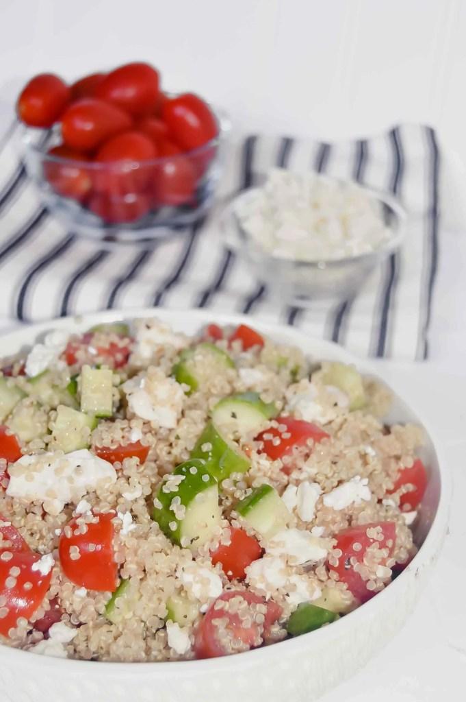 Quinoa Salad with Cucumber, Tomato  and Feta with a bowl of tomatoes and a bowl of feta on a black and white towel. www.atwistedplate.com
