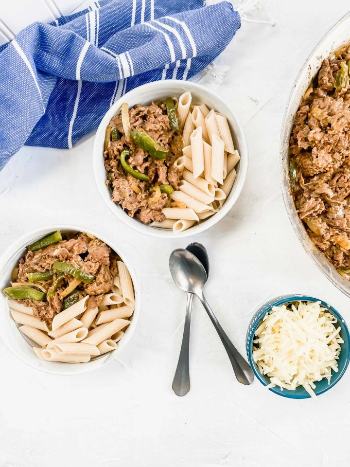 image is two bowls of pasta and with part of the pan  and a blue towel.   www.atwistedplate.com/cheesesteak-pasta/