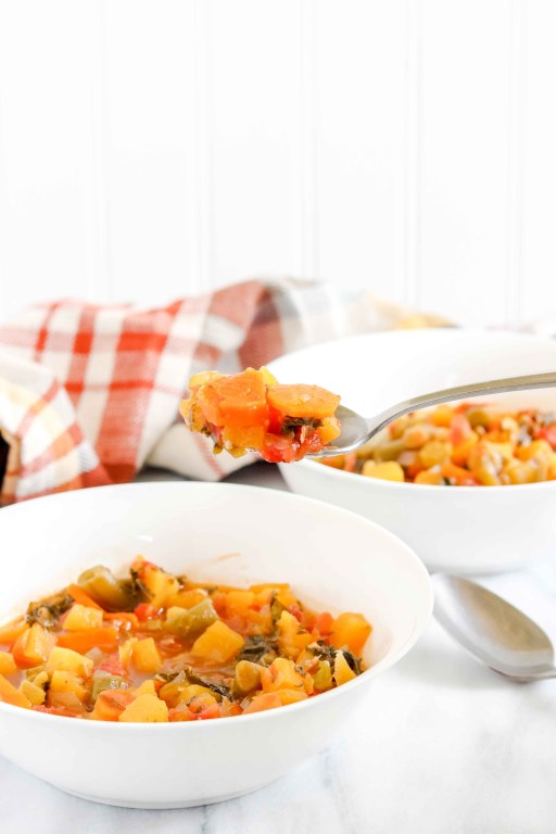 Two Bowls of Veggie Soup against a Marble background with a spoon of soup.  Behind the bowls is fall colored plaid towel.  https://www.atwistedplate.com/harvest-veggie-soup/