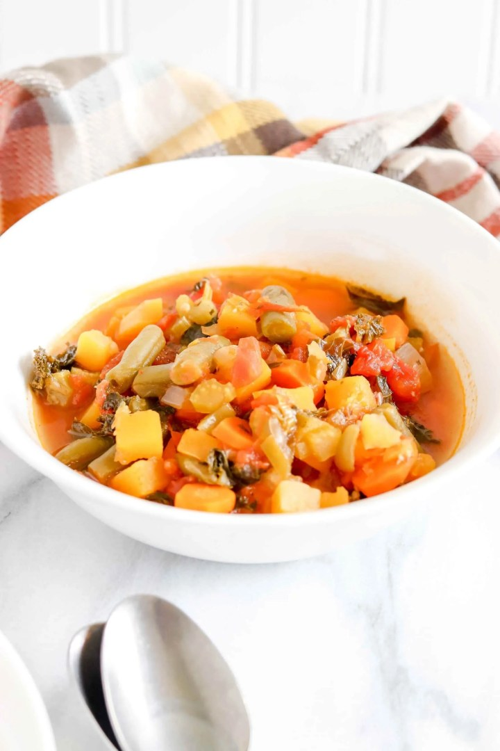 Two Bowls of Veggie Soup against a Marble background with two spoons stacked below.  Behind the bowls is fall colored plaid towel.  https://www.atwistedplate.com/harvest-veggie-soup/