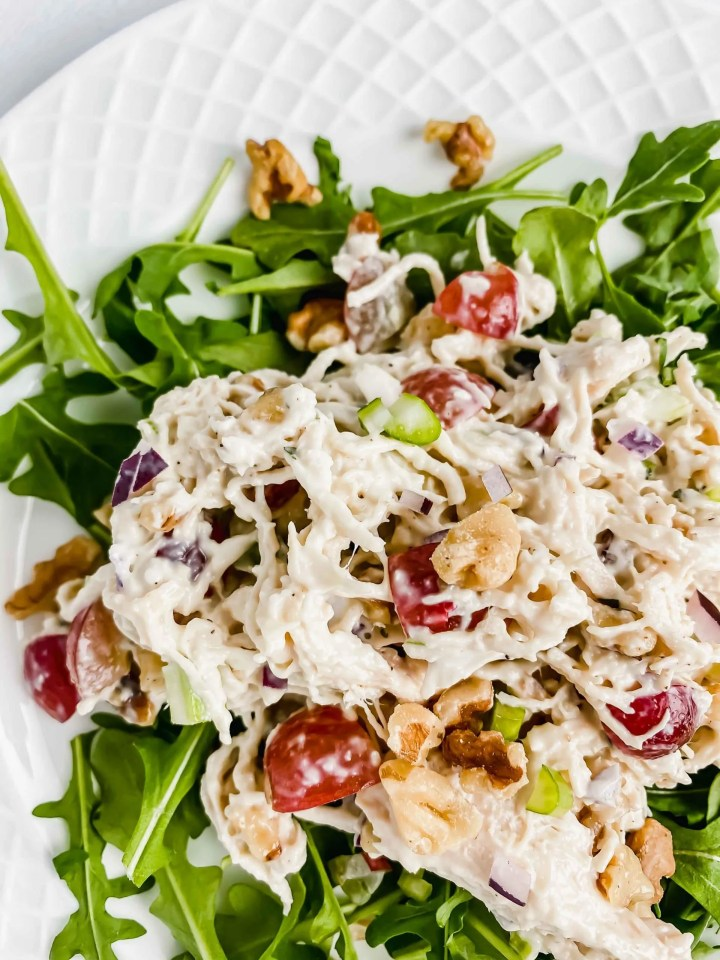 Side view of Chicken Walnut and Grape Salad on a bed of Arugula on a white plate. There is a blue and white towel along the top with Grapes and Walnuts along the bottom of the image. https://www.atwistedplate.com/chicken-walnut-and-grape-salad/