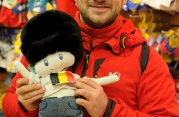 Michel tient Monde (avec un bonnet de la garde anglaise) dans une boutique à Londres. La mascotte réalisée par les enfants voyagera avec nous pendant le tour du monde