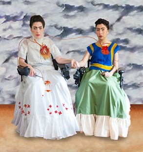 "A recreation of Mexican artist Frida Kahlo's1939 painting ""Las dos Fridas."" Two women of color, Reveca Torres and Mariam Pare, are seated in their power wheelchairs side by side. The women are holding hands. Their faces are made up to resemble Frida Kahlo, including her iconic dark eyebrows. The woman on the left is wearing a white Tehuana dress and the woman on the right is wearing a blue and red dress contemporary to the time. Both women's hearts are visible, and connected to one another by an artery. The woman on the left's heart is torn open, and she is holding surgical pincers to staunch the blood dripping on her dress."