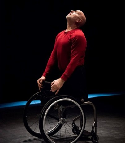 Muscular, middle-aged, bald, white man in bright red, long-sleeve shirt and black shorts in profile in a black box theatre. He is in his wheelchair, seated backwards, with his hands on the backrest of his wheelchair. He is gazing up.