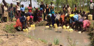 Sivan Ya'ari mit Bukadukha Dorfbewohnern in Uganda sammelt schmutziges Wasser aus den alten Wasserquellen. Foto Innovation: Africa